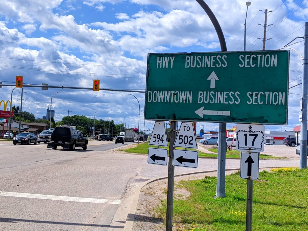 """Sign next to traffic lights that reads """"highway business section"""" with arrow pointing forwards and """"downtown business section"""" with arrow pointing left."""
