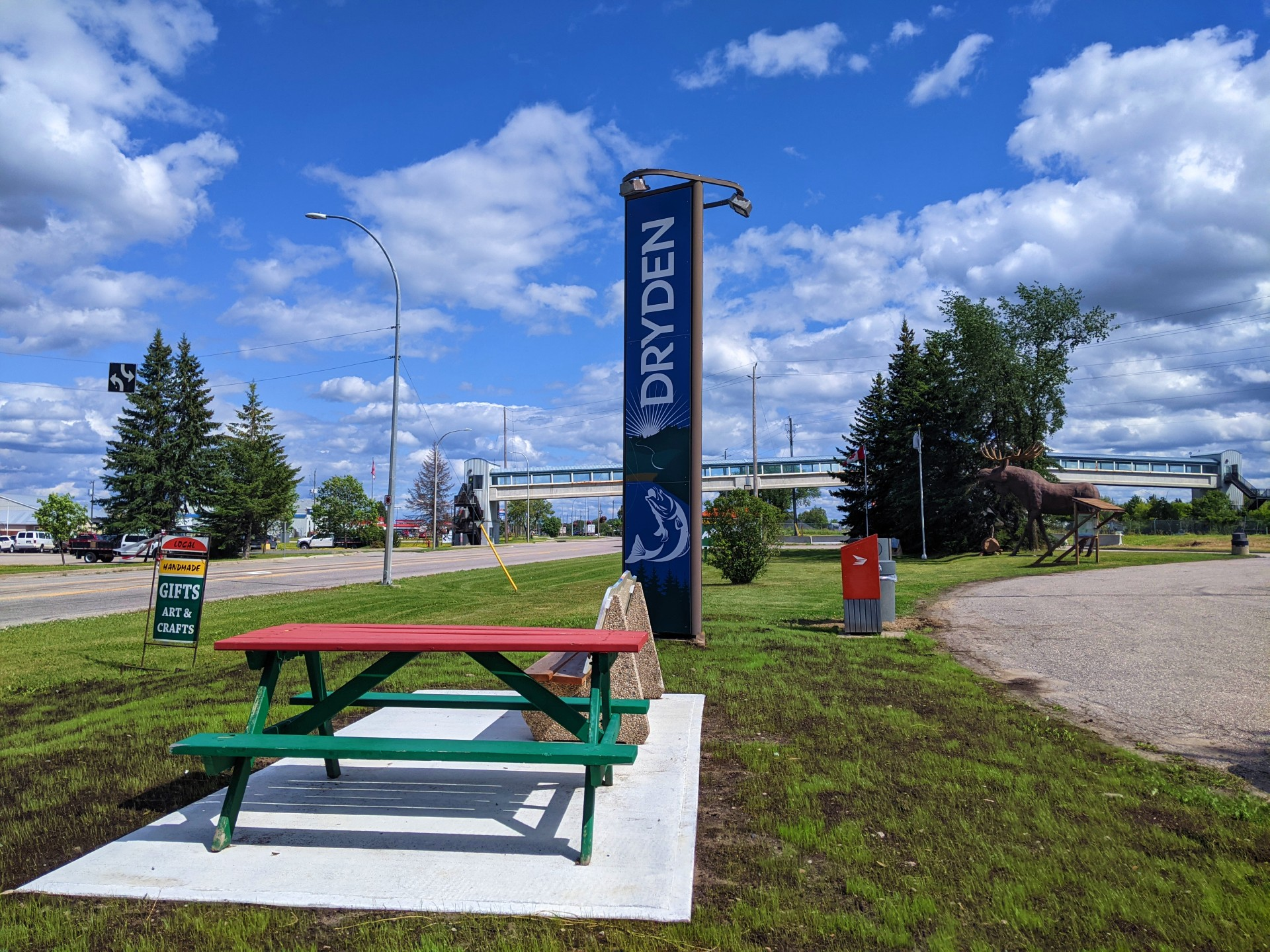 Tall, vertical Dryden sign with a silhouette of a fish on the bottom of the sign. Picnic bench in foreground. Trans Canada Highway to the left.