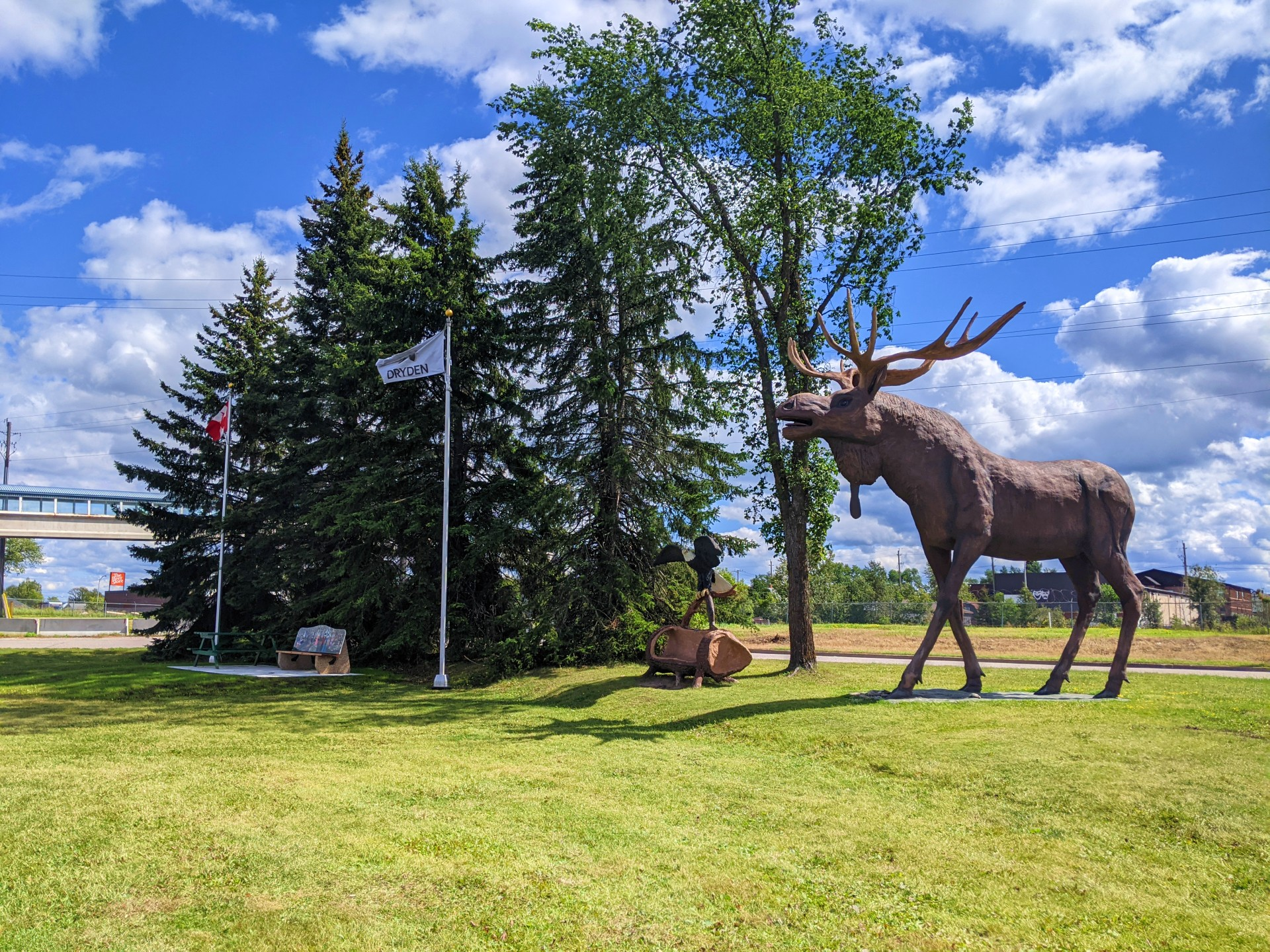 Large moose statue on the right side known as Max the Moose. Statue of eagle on a log in the middle. Dryden flag and Canadian flag on the left.